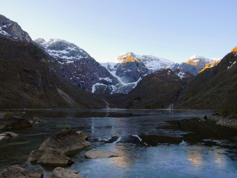 Zamrzlé jezero Bondhusvatnet, za ním mezi horami pozůstatek ledovce
