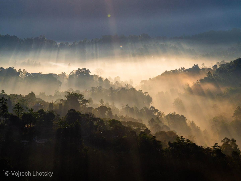 Sluneční paprsky prorážejí mlhu v údolí pod pohořím Knuckles