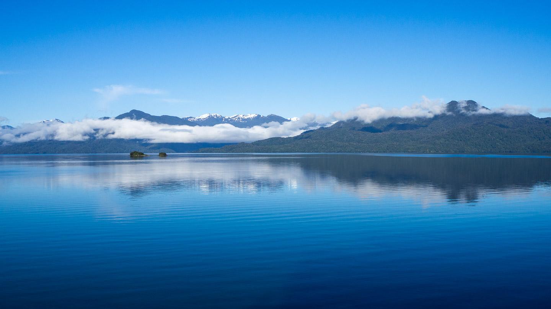Ráno projíždíme kolem klidné hladiny fjordu u NP Queulat