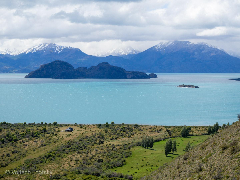 Špičaté vrcholky hor na opačné straně tyrkysového jezera